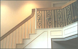 Photo of stair with half wooden balusters and half wrought iron balusters
